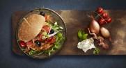 Grillburger med mozzarella og bacon på grillen